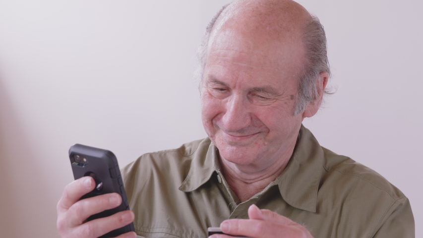 Smiling older caucasian man holding credit card and smartphone sitting on couch at home. Happy male shopper using instant easy mobile payments making purchase in online store. Royalty-Free Stock Footage #1056448097