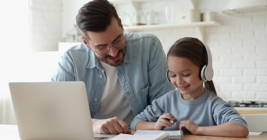 Caring young father helping little primary school learner daughter doing homework, e-learning indoors. Smiling parent explaining education program to small girl in headphones, online study concept. Royalty-Free Stock Footage #1056450464