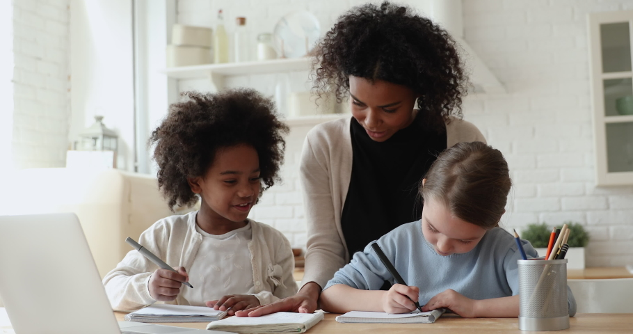 Smiling little cute diverse primary school girls studying with african american female teacher at home. Pretty young biracial foster mother helping two small mixed race daughters with homework. Royalty-Free Stock Footage #1056450476