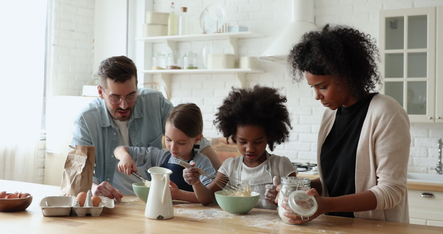 Little cute focused multiracial kids girl wearing aprons, learning making dough for pastry with affectionate loving mixed race parents, interracial family involved in hobby together in modern kitchen. Royalty-Free Stock Footage #1056450491