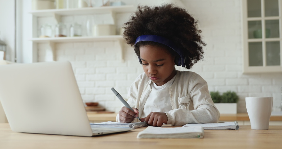 Little adorable focused afro american schoolgirl wearing headphones, studying remote online from home. Concentrated small mixed race kid girl using computer application, learning at video class. | Shutterstock HD Video #1056450500