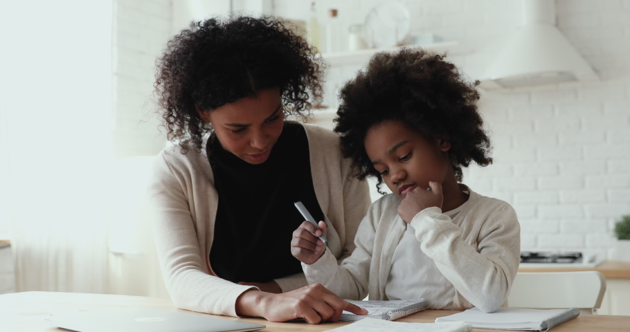Happy young biracial mother nanny babysitter helping little daughter pupil preparing for test. Focused small afro american primary school girl doing homework with smiling mommy, distant education. Royalty-Free Stock Footage #1056450515
