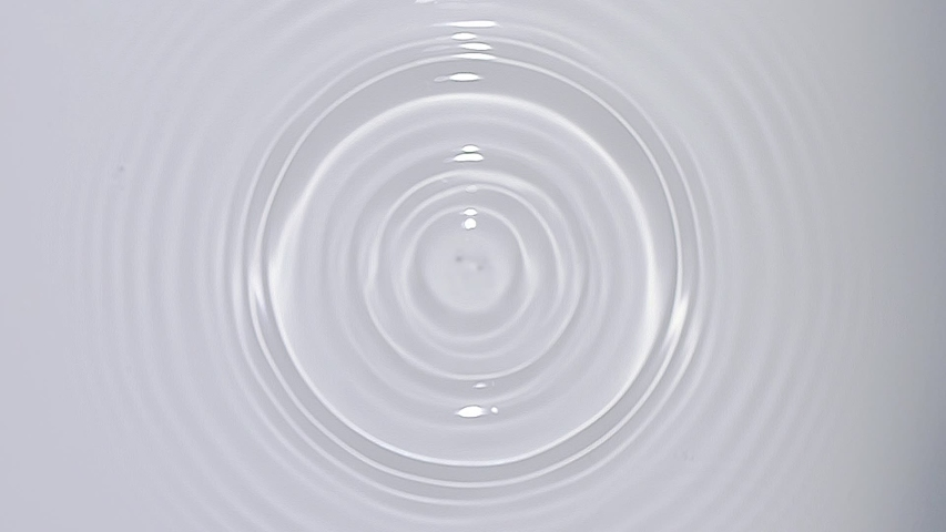 Top view of drop falls into water and diverging circles of water on white background in slow motion