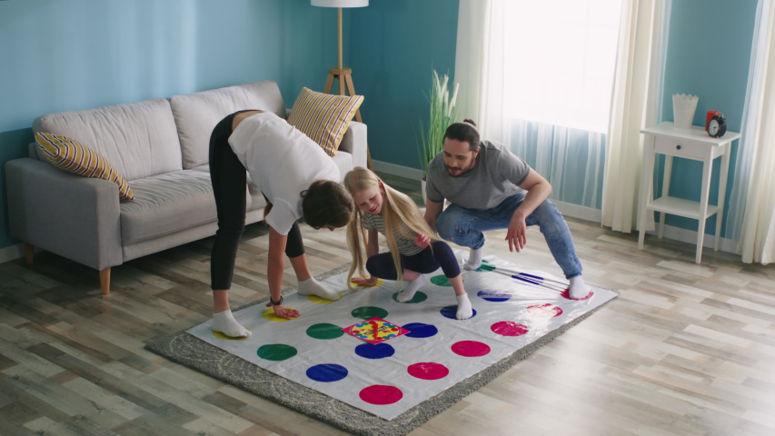 Happy young family plays interesting active game twister at home, spend time actively, enjoy their relationship, have great time together, Slow motion. Royalty-Free Stock Footage #1056468554