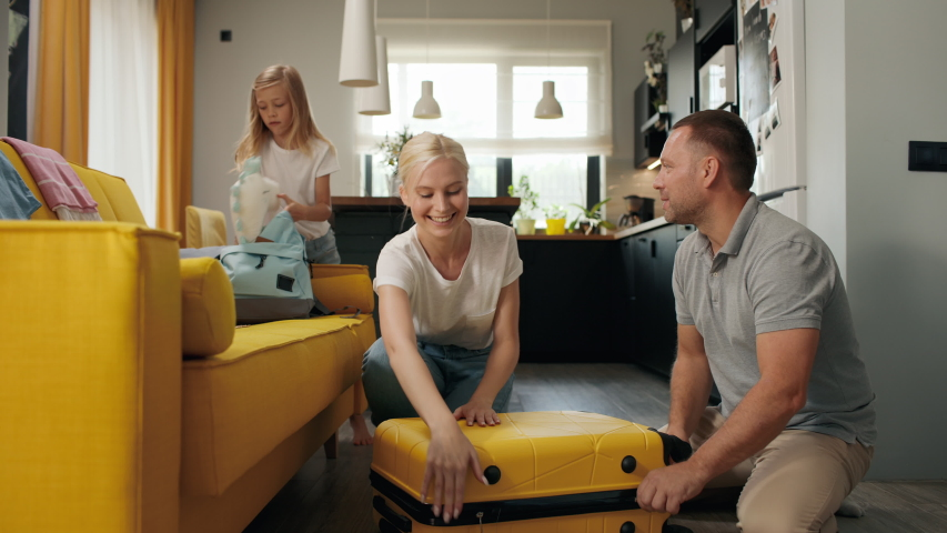 Happy family puts clothes in travel suitcase indoors of new home room. Smiling girl takes things for summer vacation. Beautiful mom closes baggage before departure or plane flight. Joy of family love
