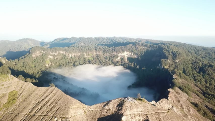 A drone capture of an early morning over the Kelimutu Lakes on Flores, Indonesia. The volcanic lakes are located in volcanic craters. One of the lakes is covered with fog. Golden hour. Calmness