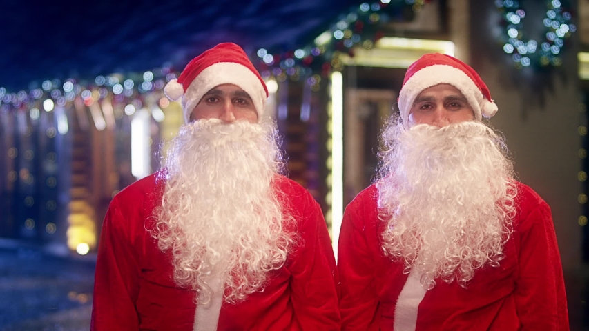 Portrait of two Santa Clause . After work or giving gifts two happy Santa Claus twin brothers removing hat , fake beard near the wooden cottage . Funny twin santa clauses giving a high five . | Shutterstock HD Video #1056472316