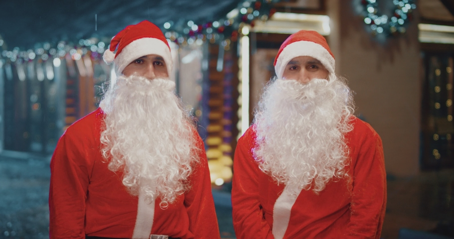 Portrait of two Santa Clause . After work or giving gifts two happy Santa Claus twin brothers removing hat , fake beard near the wooden cottage . Funny twin santa clauses giving a high five . | Shutterstock HD Video #1056472346