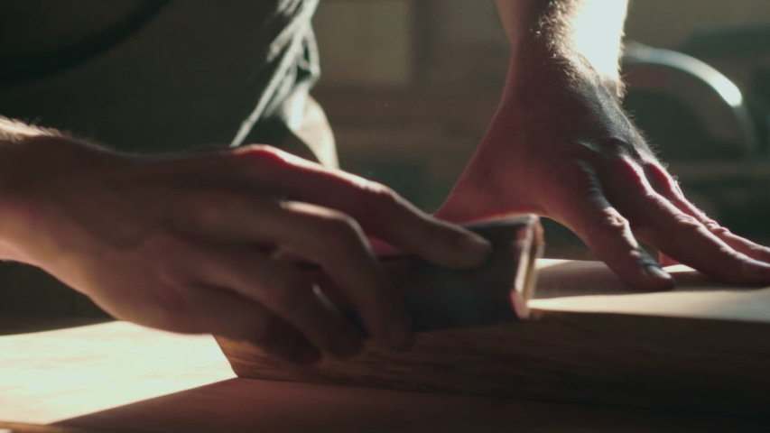 Sandpaper is sanding wood on work bench, as handse it around. Backlit by sunlight, sawdust floats up, HD slow motion. | Shutterstock HD Video #1056479345