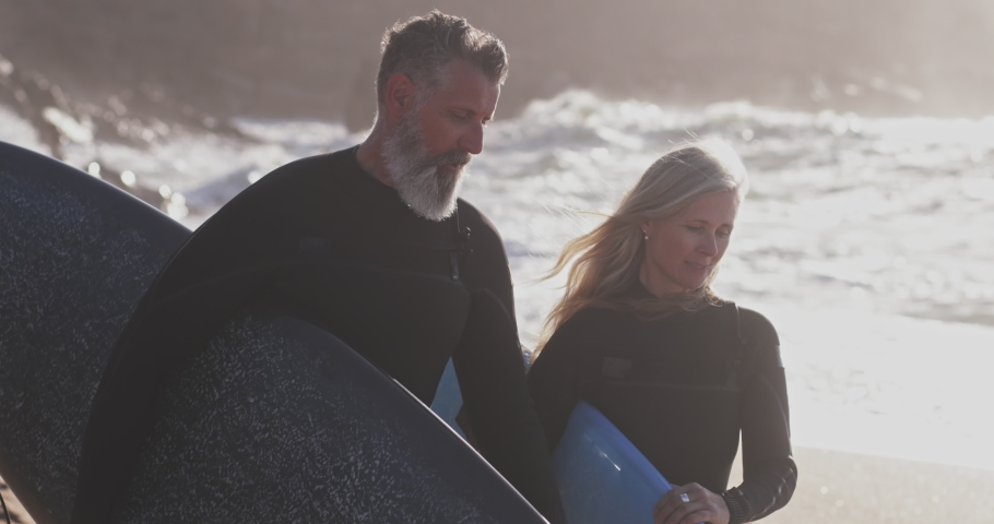Close up senior man and woman carrying surfboards at beach Royalty-Free Stock Footage #1056480200