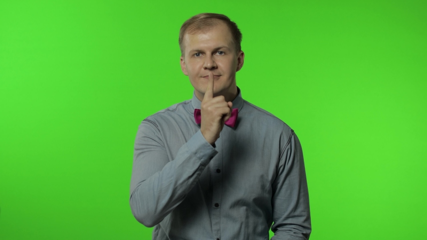 Guy putting finger on lips making silence gesture, asking to keep secret. Shh. Be quite. Portrait of man 30s posing in shirt isolated on chroma key background in studio. Green screen. People emotions