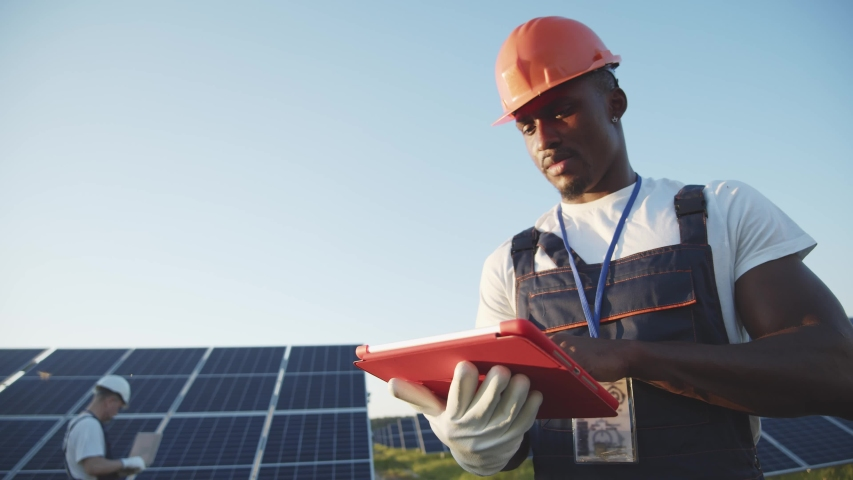 Black energy specialist using digital tablet reading information to check the efficiency of solar panel construction. Green energy jobs. Technology. Innovation. Royalty-Free Stock Footage #1056485696