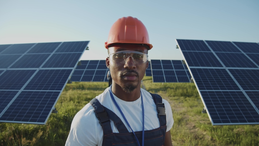 Portrait of afro-american ecology worker in hard hat standing at solar panel field. Industrial people. Sustainable energy. Technology. Royalty-Free Stock Footage #1056485732