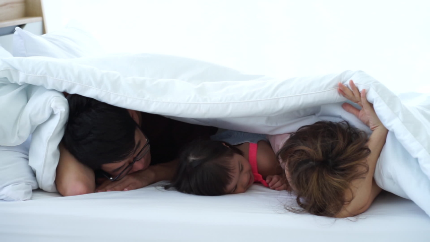 autistic disorder little girl played with parents on the white bed hiding under white blanket in the house new normal social distancing Royalty-Free Stock Footage #1056486041