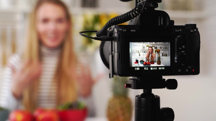 Camera screen recording - focus transition - Food blogger cooking fresh vegan salad of fruits in kitchen studio, filming tutorial. Female influencer holds apple, pineapple, talks about healthy eating. Royalty-Free Stock Footage #1056486803