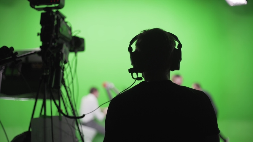 Film crew in green studio shooting video. Chroma - technology of combining two or more images or frames in single composition. Cameraman,director,crew. Filmmaking industry. | Shutterstock HD Video #1056495029