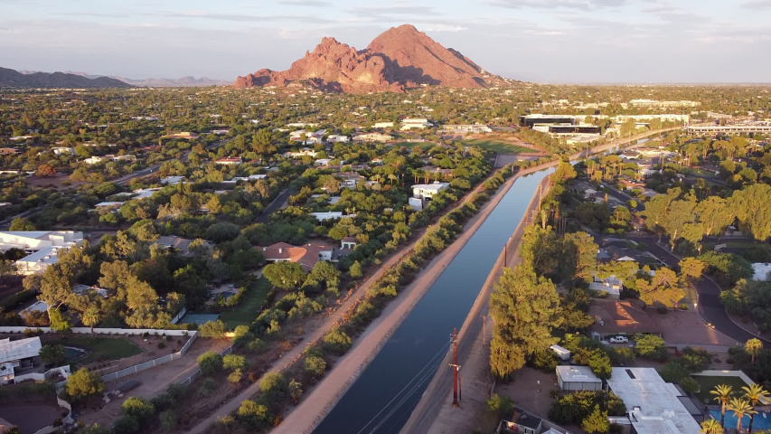 Aerial footage of Phoenix, Arizona with Camelback Mountain glowing red in the evening sun.