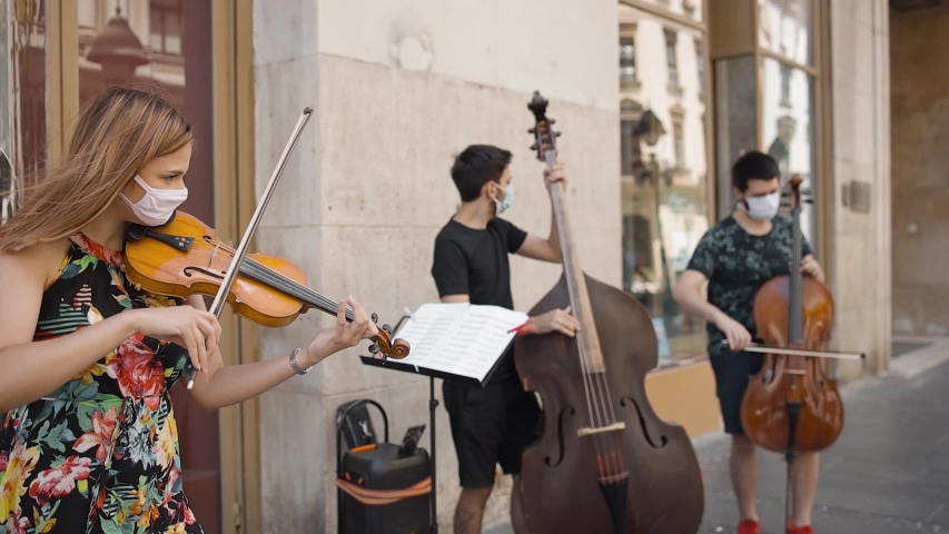 Trio strings musical band wearing protective masks playing music outside in the street in pedestrian zone in pandemic time