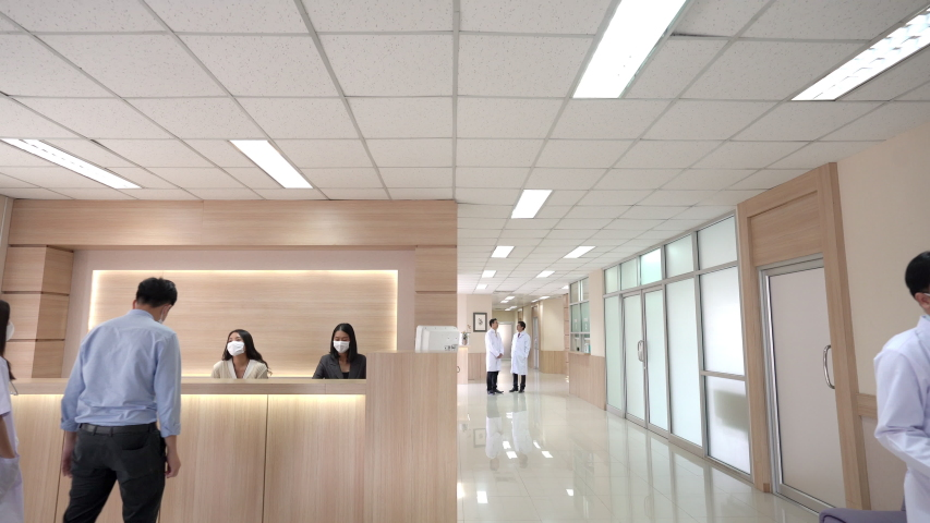 Wide shot of Lobby waiting area in modern hospital or healthcare facilities with patient at information counter and group of professional doctors and nurses working in medical center health services.