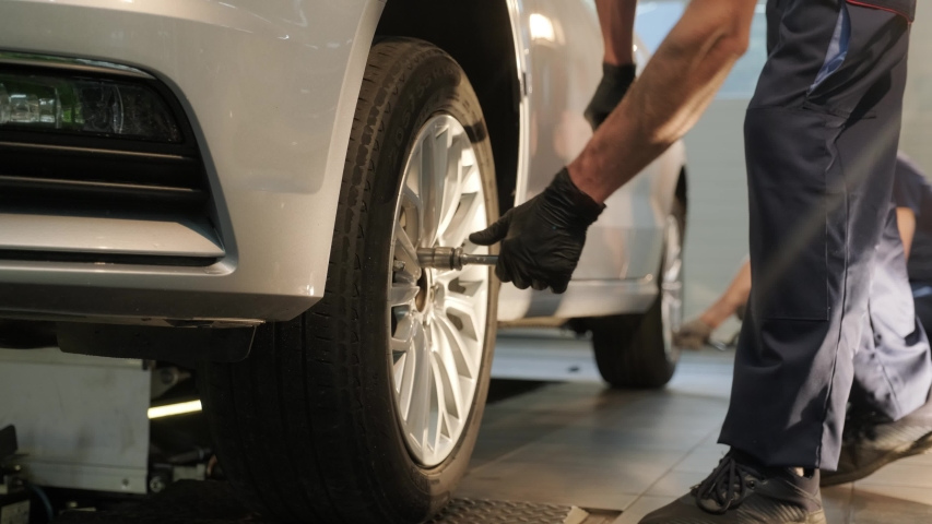 Car mechanic replacing a car tire in garage workshop. Slow motion. Auto service | Shutterstock HD Video #1056508865