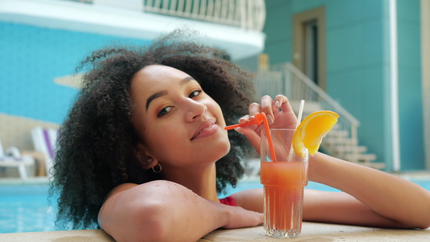 African american woman in red swimsuit drinking non-alcoholic orange cocktail from straw, relaxation sitting in pool water, smiling at camera. Ethnic Girl enjoying vacation at luxury hotel in heat