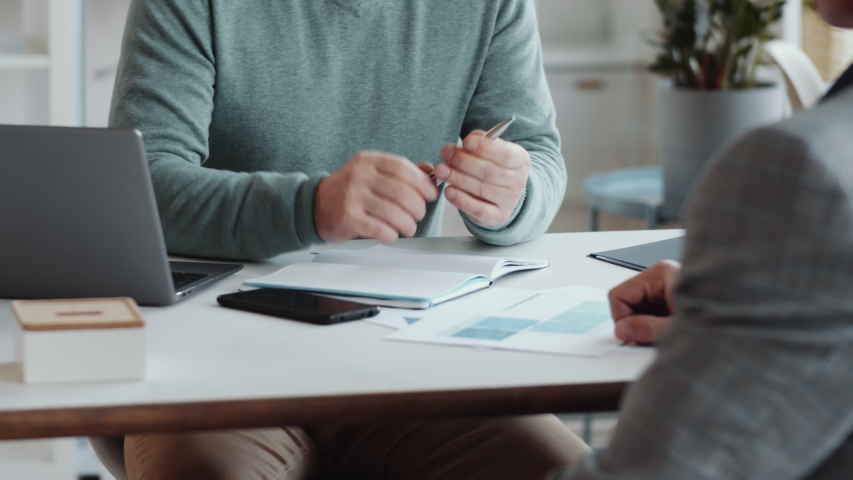 Tilt up shot of senior executive shaking hands with male business partner, speaking and signing contract while sitting at desk in the office Royalty-Free Stock Footage #1056510314