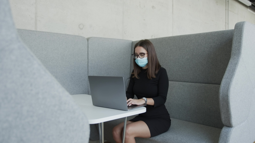Woman in mask working on laptop in cubicle and social distancing