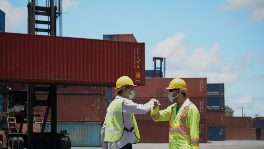 Engineer team and construction worker wear hard hat and mask and greeting Fist Bump in workplace such as container or industry.  Protect from COVID-19 coronavirus While working, healthcare concept Royalty-Free Stock Footage #1056511034