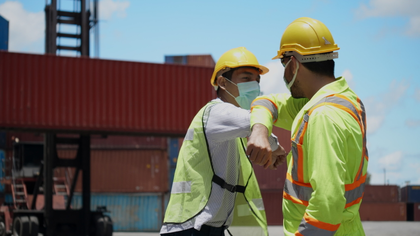 Engineer team and construction worker wear hard hat and mask and greeting bumping elbow in workplace such as container or industry. Protect from COVID-19 coronavirus While working, healthcare concept Royalty-Free Stock Footage #1056511037