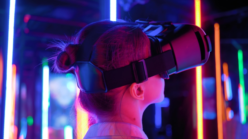 VR, futuristic, retrowave, immersive, entertainment concept. Woman using virtual reality headset and looking around at interactive technology exhibition with colorful illumination - back view Royalty-Free Stock Footage #1056519185