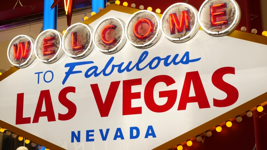 Welcome to fabulous Las Vegas retro neon sign in gambling tourist resort, USA. Iconic vintage glowing banner, symbol of casino, games of chance, money playing and hazard bets. Illuminated signboard. | Shutterstock HD Video #1056526055