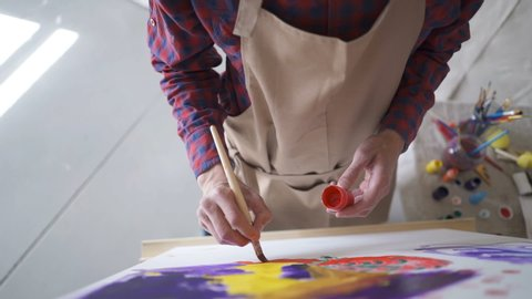 The artist paints on canvas and smears a brush. Canvas stands on the easel.
