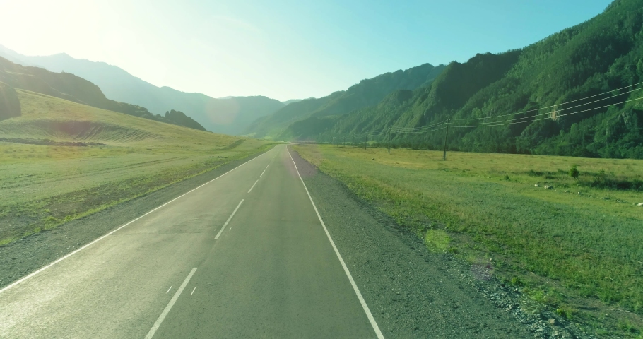 Aerial low air flight over mountain perfect asphalt highway road and meadow at sunny summer morning. Near green trees. Fast horizontal movement with sun rays.   Shutterstock HD Video #1056527627