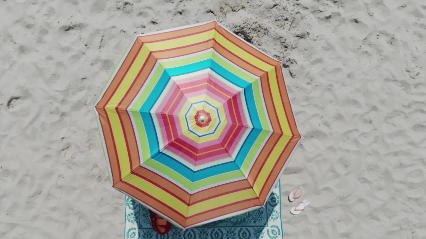 Top view on a sun lounger under an umbrella on the sandy beach. Concept of summer vacation