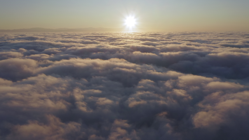 Camera is raising above from the thick fog above the beautiful ocean of clouds at sunrise. Sun is rising above the endless sea of clouds until the horizon. Amazing nature landscape, 4K drone in sky Royalty-Free Stock Footage #1056529145