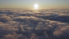Camera is raising above from the thick fog above the beautiful ocean of clouds at sunrise. Sun is rising above the endless sea of clouds until the horizon. Amazing nature landscape, 4K drone in sky