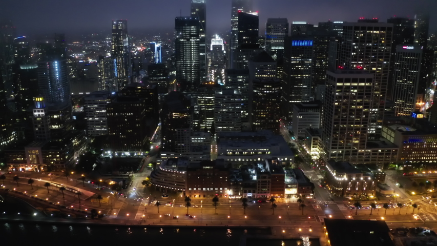 Aerial panorama of Embarcadero and Financial District skyscrapers and buildings, downtown San Francisco, dark summer night light. 4K b-roll drone shot of night scene. Illuminated night city, USA