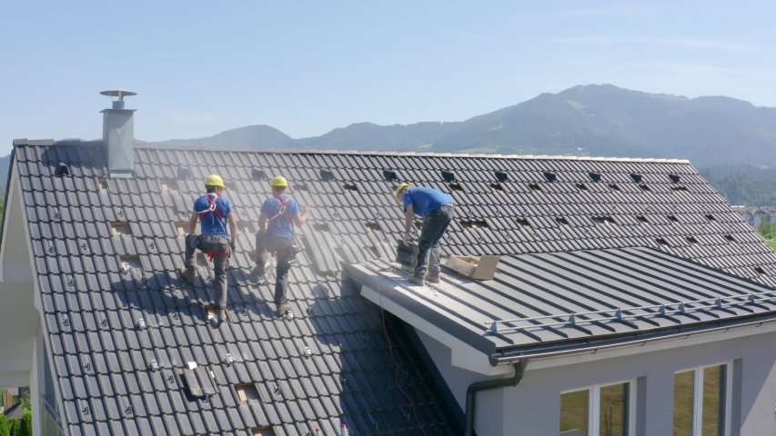 Blue Collar Tilers Repair Roof Of A Middle Class Suburban House