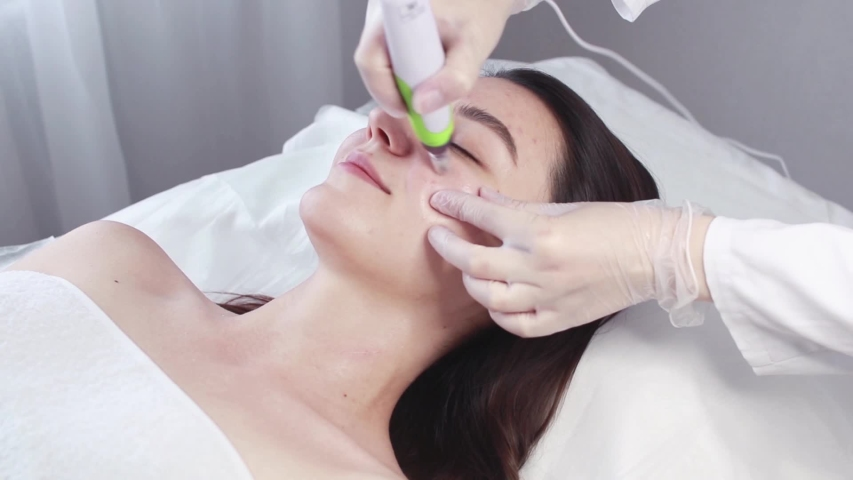 Fractional mesotherapy. A young woman in the cosmetologist's office receives fractional mesotherapy for her face. Rejuvenation of the skin of the face. Acne treatment.Hardware cosmetology. Beautician. | Shutterstock HD Video #1056529406