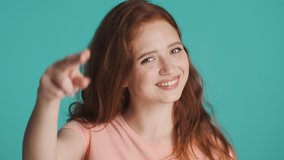 Pretty smiling redhead woman happily showing see you later gesture on camera over colorful background