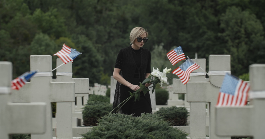 Woman putting white lily flower on grave at cemetery. Widow in dark glasses looking to camera while standing in row of stone crosses with american flags. Concept of memorial day.