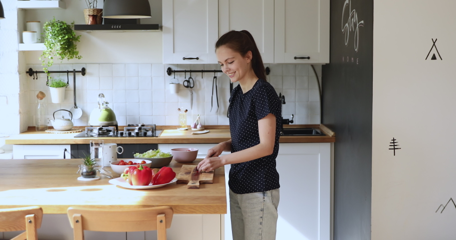 Lively funny young woman moves to music feels carefree while preparing vegetable salad, cuts cherry tomato put in bowl dancing in domestic kitchen. Stay, cook, eat at home, healthy lifestyle concept