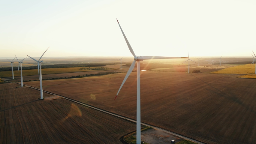 Large wind turbines with blades in field aerial view bright orange sunset blue sky wind park slow motion drone turn. Silhouettes windmills, large orange sun disc summer lens flare. Alternative energy Royalty-Free Stock Footage #1056539327