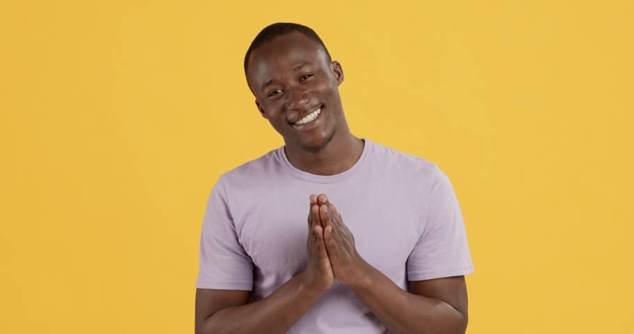 Grateful black man clasping hands and smiling, touched by complement, namaste gesture