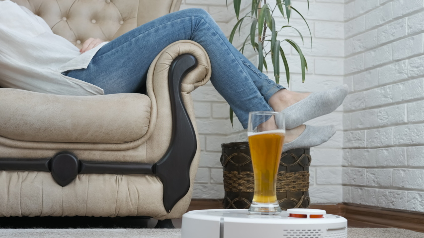 Beer on a robot vacuum cleaner. Home assistant concept. A woman takes a glass of beer on a smart vacuum cleaner. Royalty-Free Stock Footage #1056539726