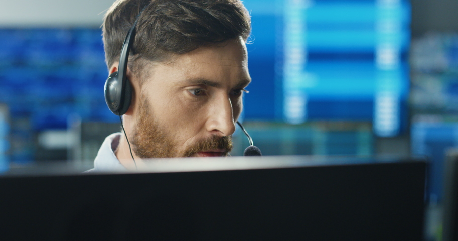 Close up of young Caucasian mman trader in headset working at monitor computer and talking with client in trading office. Male broker having conversation. Exchange job. Sales manager. Royalty-Free Stock Footage #1056542132