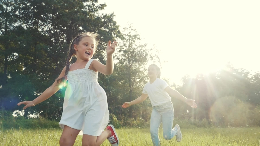 children kid dream together run in the park at sunset. happy family people in the park concept. two sisters playing catch-up run. baby child fun running in green meadow. happy family kid dream concept