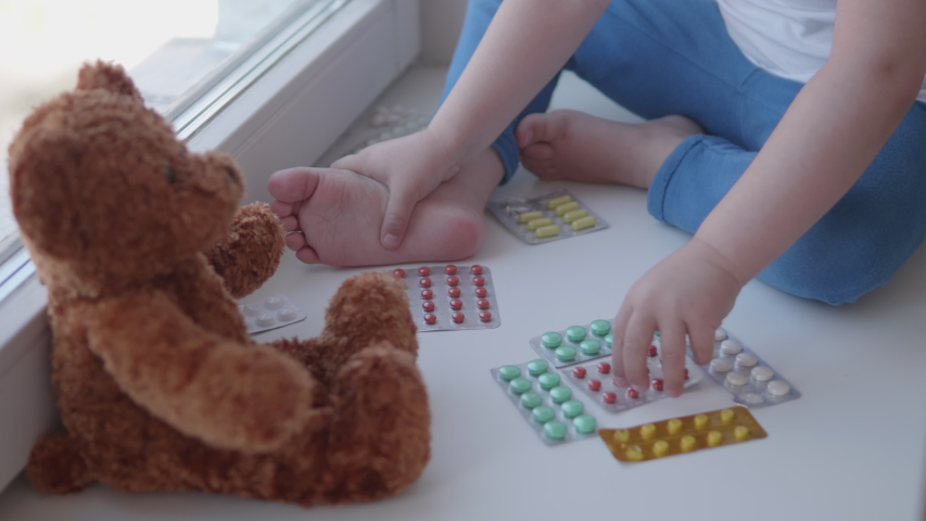 Toddler sits on windowsill and plays with scattering pills without parent's control. Dangerous situation with little boy. Medicines are freely available to child. Royalty-Free Stock Footage #1056552878