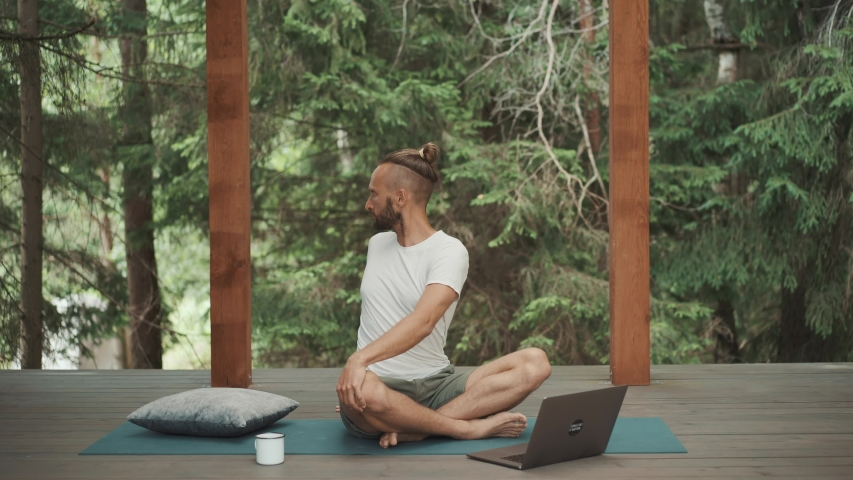 Freelance business man warming up and practice yoga workout online with teacher web course on laptop. New app for self care and healthy body. Quarantine training routine. Mindfulness lifestyle   Shutterstock HD Video #1056563309