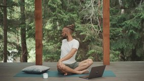Freelance business man warming up and practice yoga workout online with teacher web course on laptop. New app for self care and healthy body. Quarantine training routine. Mindfulness lifestyle